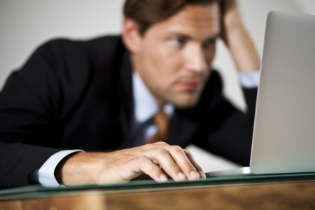 Businessman rests his head in one hand while working on laptop photo