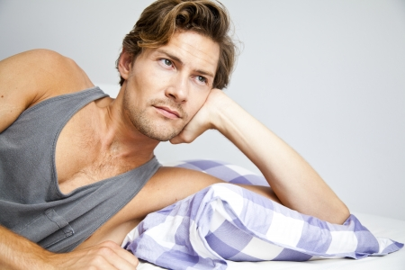 Young man lying in bed daydreaming about better times Stock Photo - 22089597