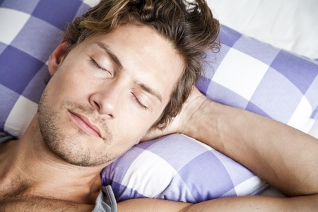 Young man lying in bed sleeping peacefully Stock Photo - 22089598