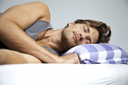 Young man sleeping peacefully in his own bed Stock Photo - 22089599