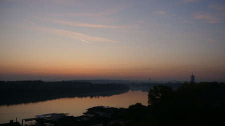 Sunrise Time Lapse on Danube River with Belgrade Serbia Buildings in Background. Blue and Orange Sky with Nature in the Landscape and Trees Reflecting on the Calm Waters of the Danube River.