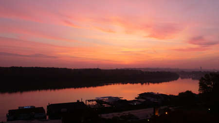 Landscape of Danube River Bank with Trees Reflecting on Water at Sunrise. Red and Yellow Sky Clouds in Timelapse with Modern and Historical Buildings of Belgrade City Downtown in the Background.
