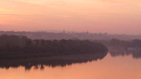 Danube River Bank Landscape with Trees Reflecting on Water at Sunrise in Timelapse with Belgrade Serbia City Downtown with Modern and Historical Buildings of Belgrade City Downtown in the Background.