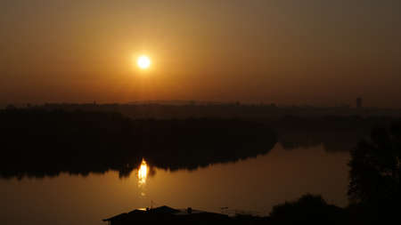 Sunrise Timelapse with Sunlight Reflections on the Danube River in Belgrade Serbia. The Silhouette of the Wall of Kalemegdan Citadel and the Orthodox Cathedral are visible on the background with the City Skyline
