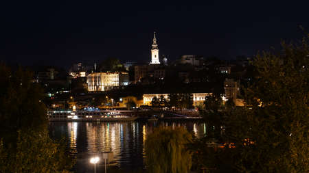 Belgrade Serbia Downtown Night Cityscape Timelapse with Light Reflections on the Sava River Water. The Serbian Orthodox Cathedral Church of St. Michael the Archangel Bell Tower is Visible.