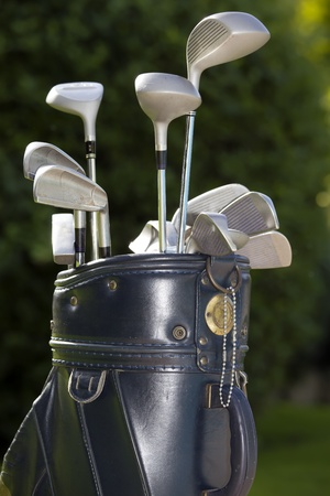 A golf bag with three or four clubs in it including a driver,iron and putter