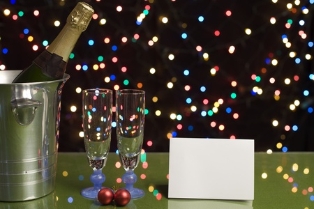 bottle of champagne with two glasses and a note on a light background