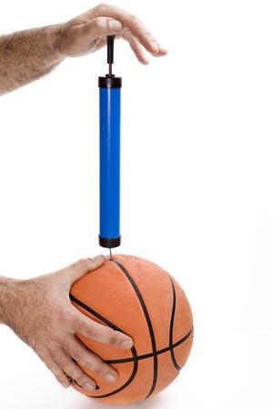 balon baloncesto: a dos manos inflar una pelota de baloncesto en un fondo blanco Foto de archivo