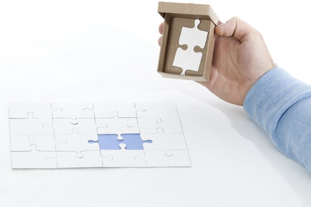 hand holding an open box containing the last piece of the puzzle, all on a white background photo