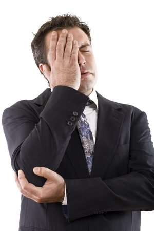 businessman with hand on face, eyes closed by an expression of concern or headache Stock Photo