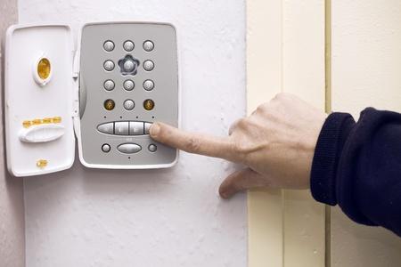 alerta: la mano de conectar la alarma de seguridad dentro de la casa Foto de archivo