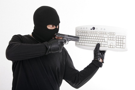 robber pointing a pistol at a computer keyboard photo