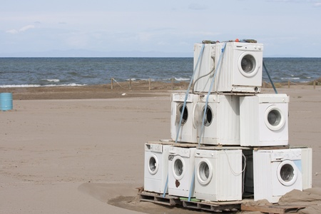 lot of old washing machines abandoned in the middle of a beach
