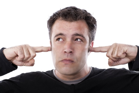 ignoring: young boy covering his ears with his fingers and grimacing, ignoring what you are saying.