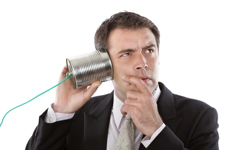 Businessman listening to a conversation from a telephone can photo