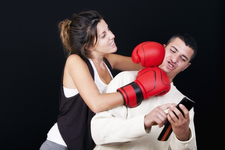 angry woman beating her husband because she is addicted to mobile  photo of humor  On a black background photo