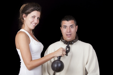 woman looking with happy face WHILE holding a chain around the neck of her husband  The husband makes expression of fright  Marriage metaphor