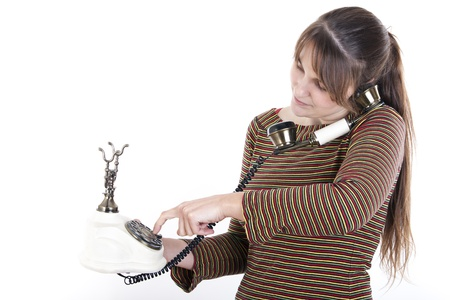 Young woman using an old white phone on an isolated background photo