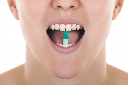open mouth of a pretty girl holding a pill, close up  photo