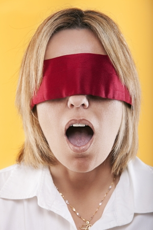 studio shot portrait of a beautiful young blindfold woman with open mouth  On a yellow background