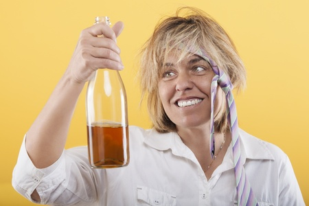 Drunk woman with bottle, badly dressed, with cheerful expression photo
