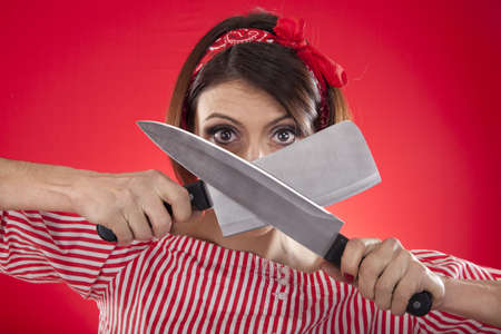 retro girl looking between two kitchen knives on a red background photo
