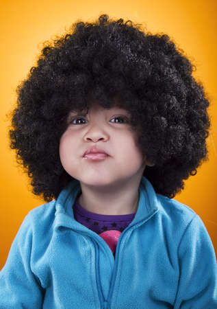 pout: 2 year old girl with an afro wig, making pout