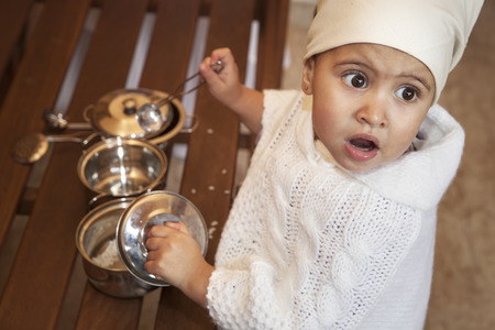 Little girl  with spoon and metal pots and cook hat. looking up photo