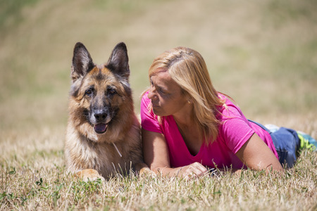 endear: Girl playing with her German shepherd dog in the park, summer. Outdoors. Beauty nature.