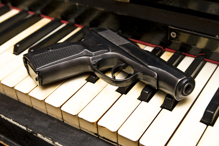 Dlack gun on the keys of piano close up image