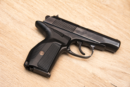 Dlack gun on the wooden background close up image