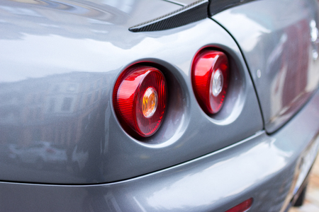 Red tail lights (rear lights, brake lights) of grey car close up image. Stock Photo