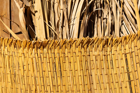 Woven straw texture with dried palm leaves on background. Handmade woven rug. flaxen weaving yellow mesh close up image.