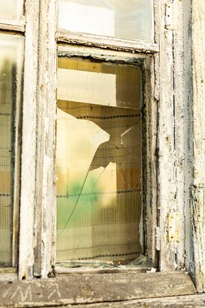 Broken Window of an old abandoned house with brick walls.