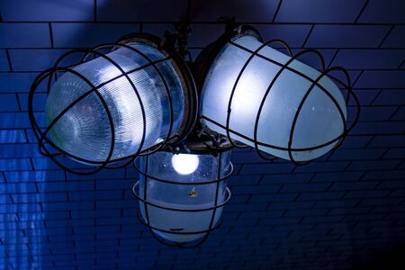 Old archaic lamps in coarse shades and wire protection caps. Rough street lights. Close up blue tones image.