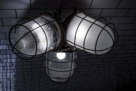 Old archaic lamps in coarse shades and wire protection caps. Rough street lights. Close up image. 스톡 콘텐츠
