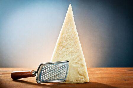 queso rallado: Pedazo de queso parmesano rallado y listo para cortar Foto de archivo