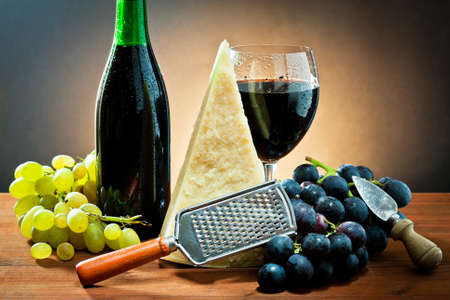 table with grapes, bottle and glass of wine, cheese and grater. photo