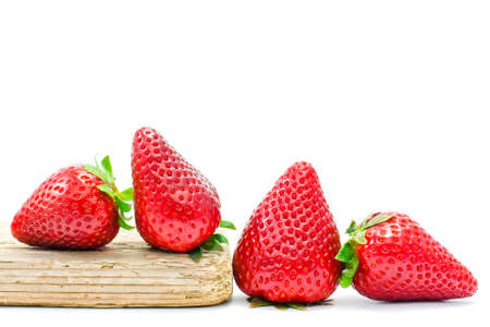 strawberry plant: group of  red strawberries on wood