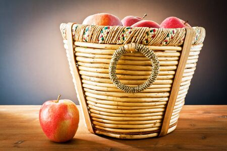 red apples on wooden basket photo