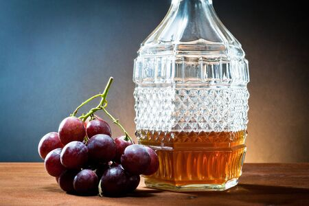 amber coloured: grapes,wine and bottle liquor  Stock Photo