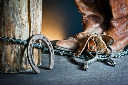 rodeo americano: Las botas de vaquero, el l�tigo de herradura, y las espuelas en la madera