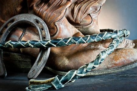 Cowboy boots,horseshoe and whip on wood  photo