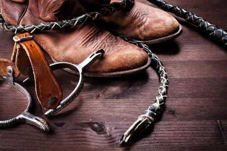 rodeo americano: Botas de vaquero látigo y las espuelas en la madera