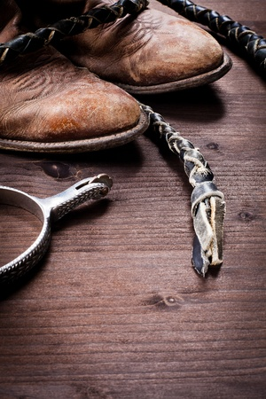 cowboy background: Cowboy boots whip and spurs on wood