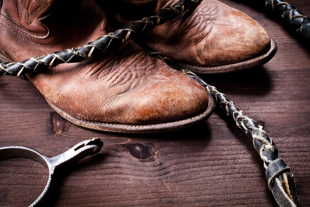 spurs: Cowboy boots whip and spurs on wood