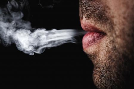 smoking a cigar: man smoking cigarette
