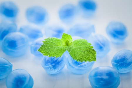 Blue candy fresh balsamic syrup with mint leaves on a white background
