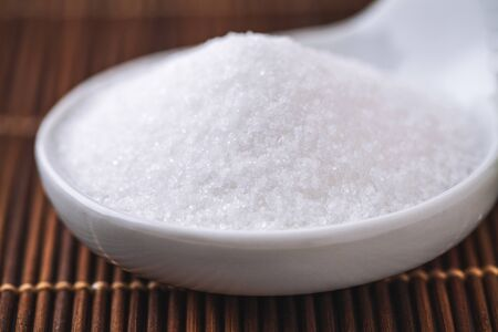 granulated: refined white sugar in a bowl on background