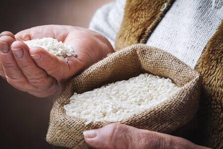white rice in old hands Standard-Bild